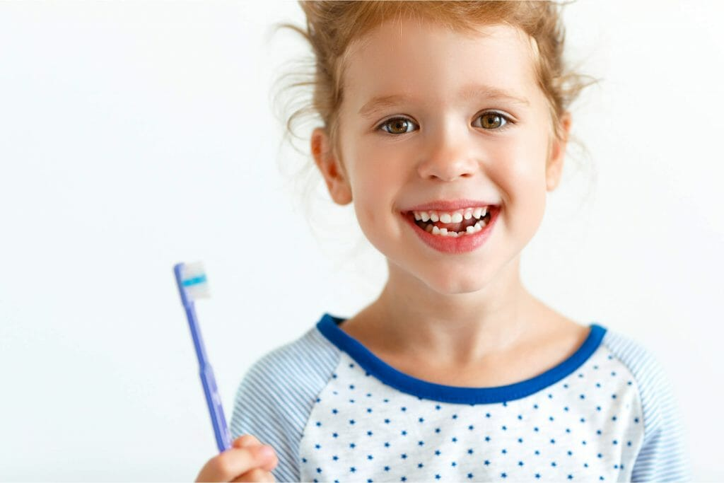 Happy girl with a toothbrush brushes teeth