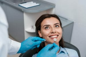 Dentist with latex gloves checking on smiling woman