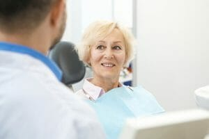 Senior woman smiling and listening to her dentist.