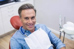 Smiling male patient sitting on dentist chair